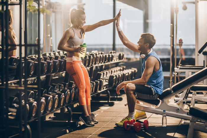 A man and woman in workout clothing high-fiving with exercise equipment in the background.