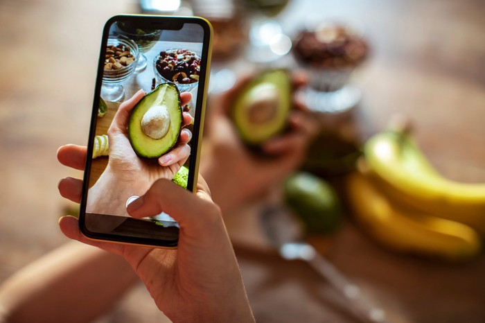 A person taking a picture of themselves holding an avocado.