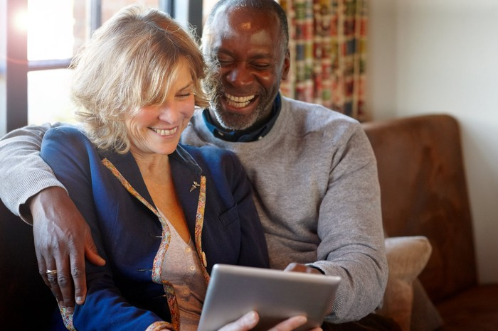 Two people sitting on a couch together smile as they look at a tablet.