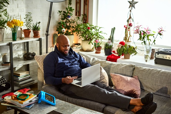 Person lounging on couch at home holds a credit card in one hand while browsing on a laptop.