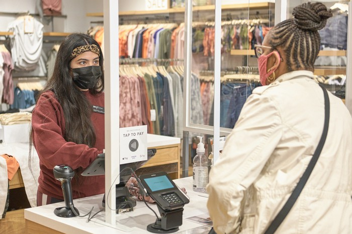 A person making a purchase by a cashier with a salesperson at a Gap Athleta store.