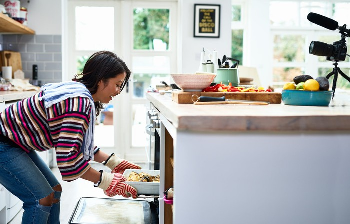 A woman taking a hot dish out of an oven in her kitchen.