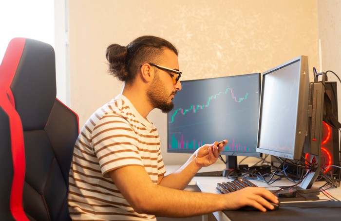 A stock trader in front of market graphs on monitors.