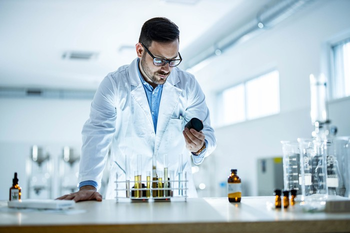 Scientist in the laboratory looking at a bottle.