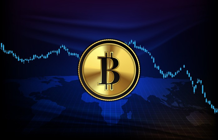 Bitcoin symbol set over a dropping stock chart.