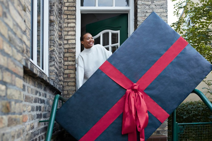 Person on doorstep behind a huge wrapped gift box.
