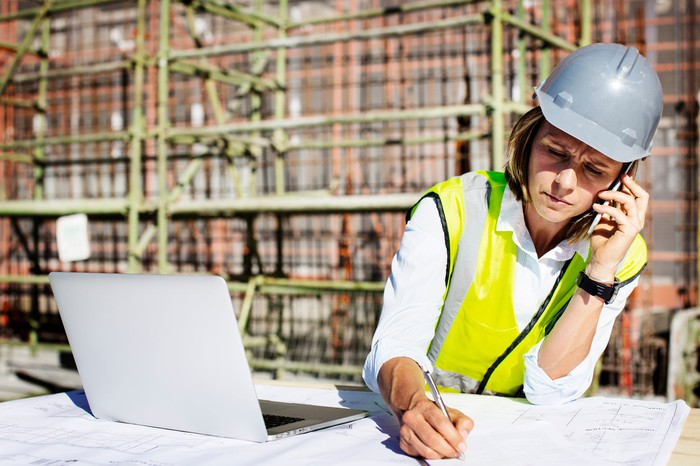 An architect talks on the phone while drafting plans on a construction site.