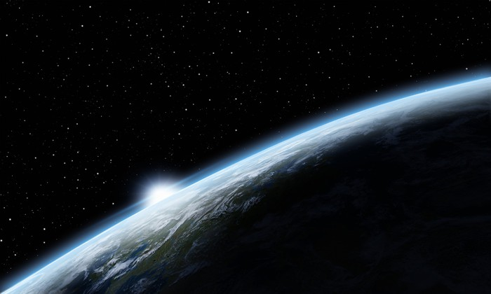 Curvature of Earth as seen from space with the sun slightly visible.