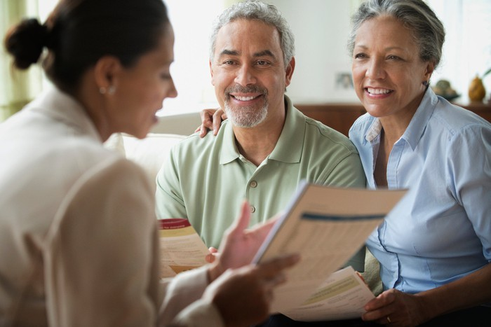 A middle-aged couple reviewing documents with an insurance broker.