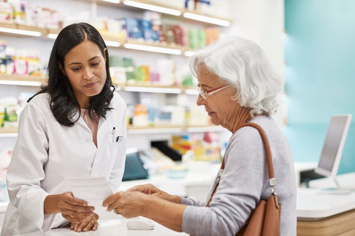 Pharmacist and patient conferring at a pharmacy counter.