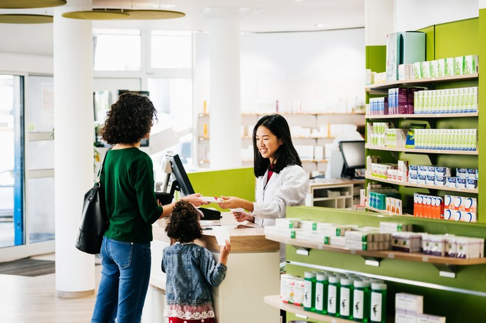 A pharmacist filling a prescription for parent and child.