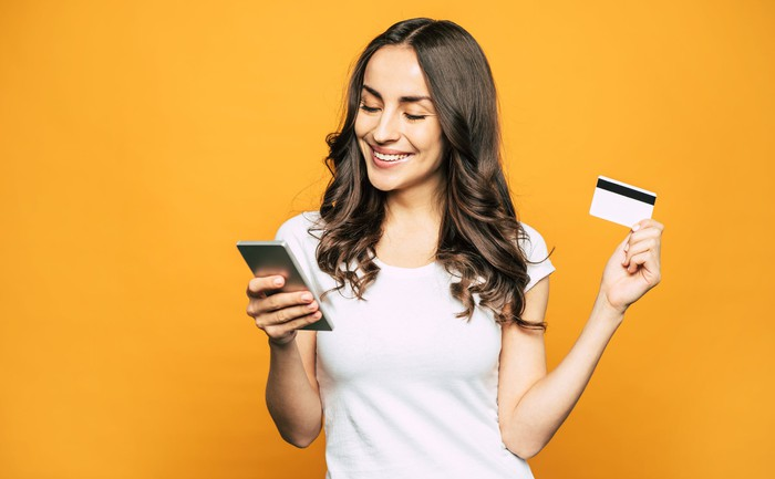 Smiling person making credit card payment on mobile device.