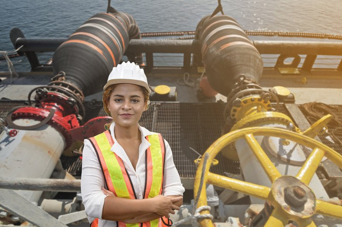 An engineer staff worker with an offshore oil load vessel background.