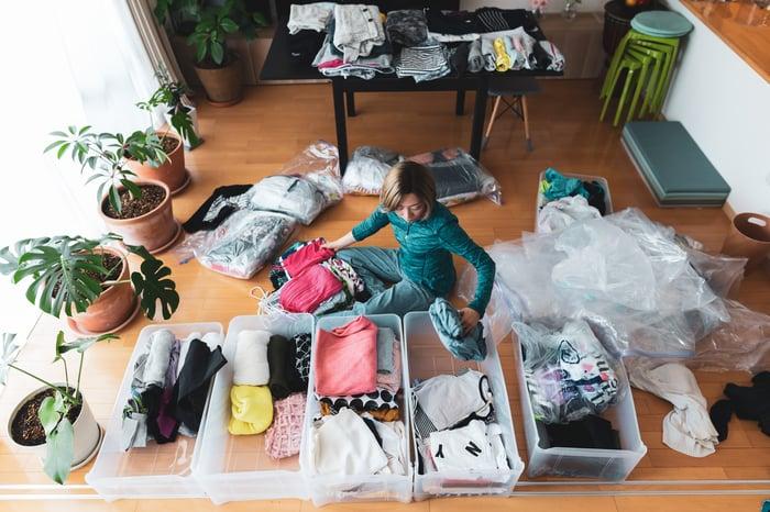 Woman sorting clothes in bin