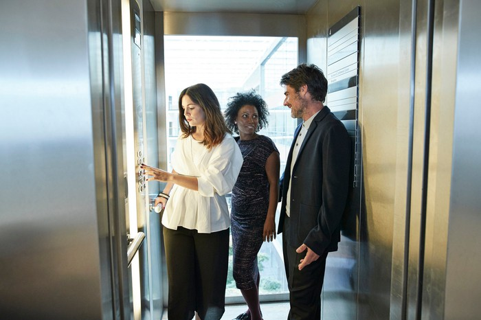 Corporate workers in an elevator.