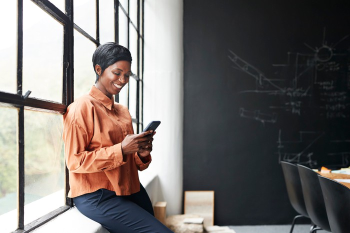A woman smiling as she looks at her phone.