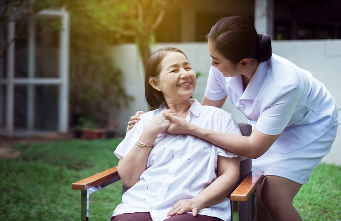 A caretaker looks after a smiling patient sitting outside in a chair.