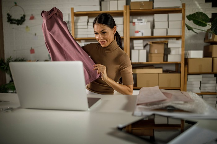 A person holding a garment in front of a computer.