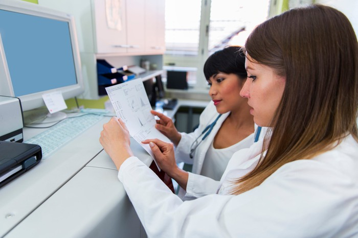 Two scientists in a laboratory consider a printout of genetic data while sitting in front of a computer.