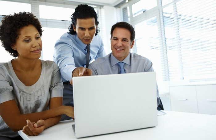 Three smiling people in office clothing crowd around a laptop, as one of them points to the screen.