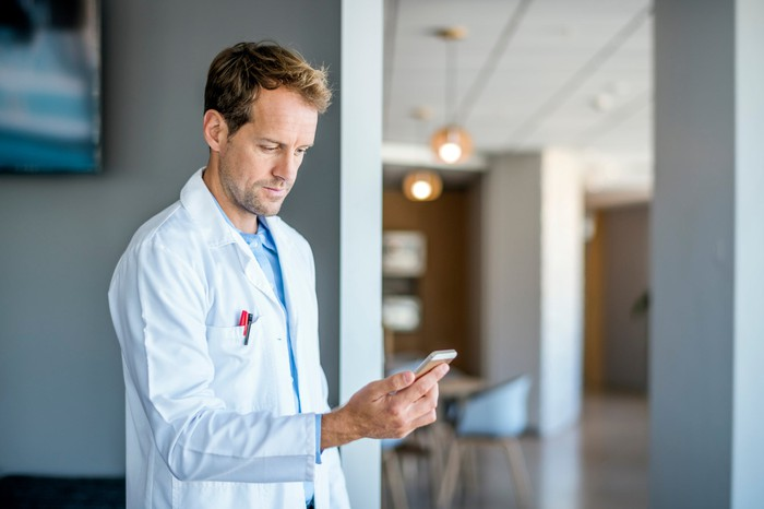 A doctor looking at a cell phone.