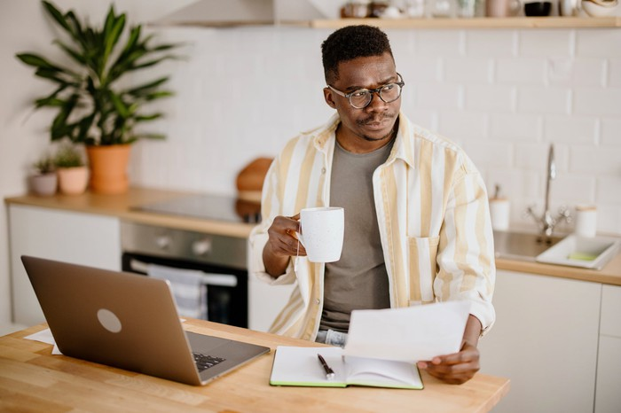Man working from home reviewing a sheet of paper.