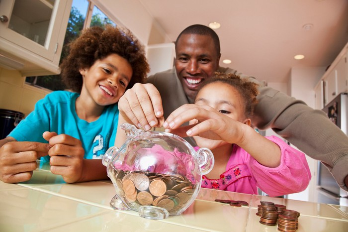 A family adding coins to a piggy bank.