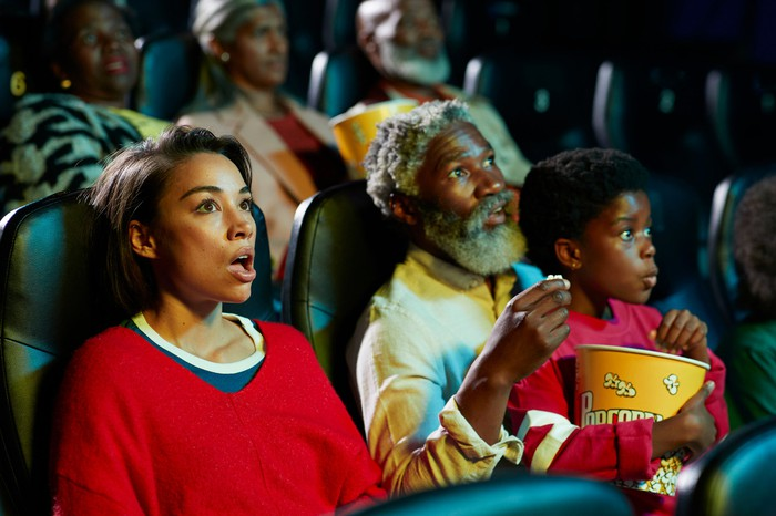 A parent, grandparent, and child holding a bucket of popcorn react with surprise while watching a movie.