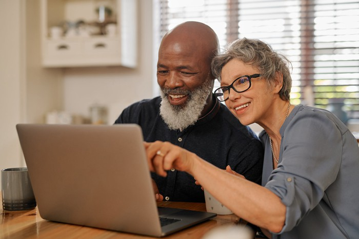 Two people smiling as they look at a laptop screen.