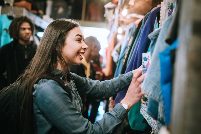 A smiling group of young adults have fun shopping for retro and vintage clothing styles at a second hand thrift store.