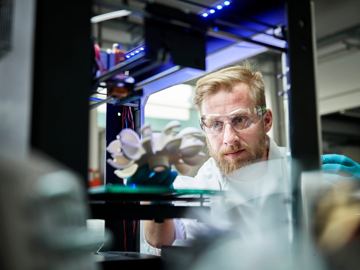 A technician looks at a metal object in a 3D printer.