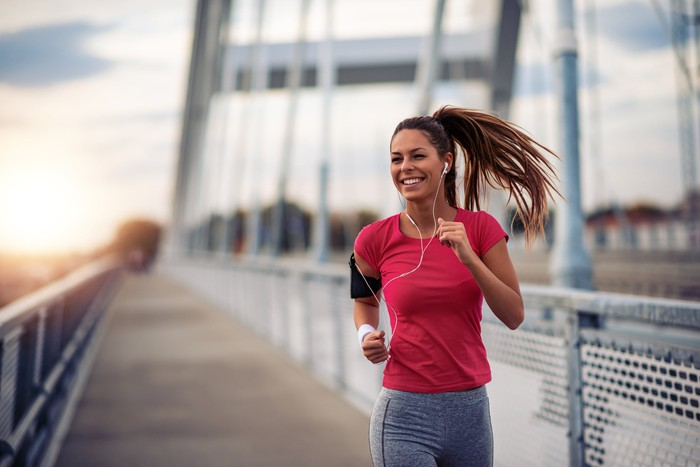 A young woman jogs over a bridge at sunrise.