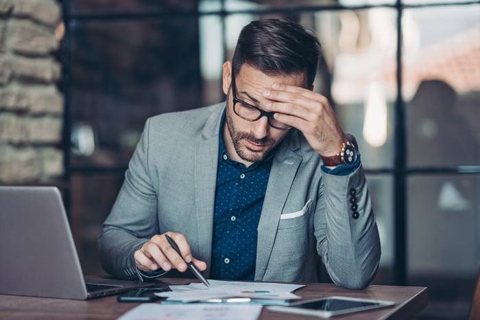 Man holding head looking at stock charts.