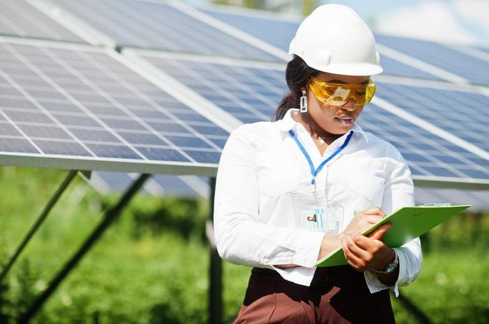 Tech worker wearing hard hat reading clipboard in front of solar panels.