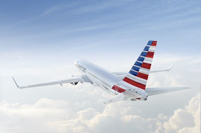 An American Airlines plane soars over the clouds.