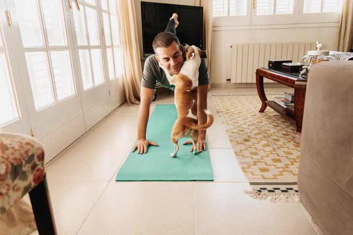 Un propriétaire d'animal s'entraine par terre et se fait serrer dans ses bras par un chien.