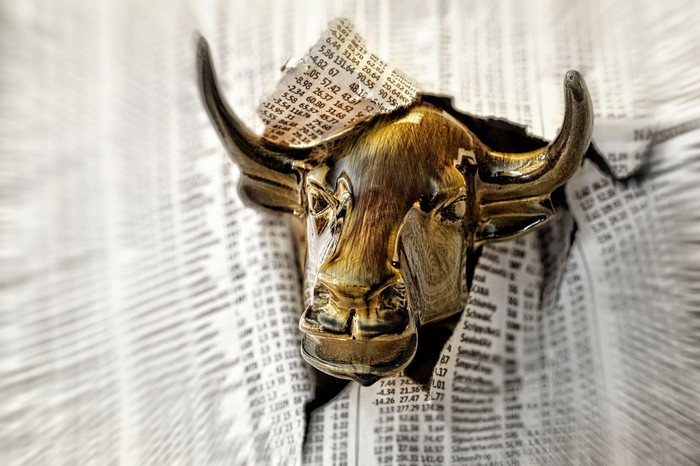 Gold bull head bursting through stock pages