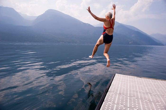 Senior woman sauter dans le lac.