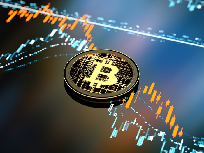 Bitcoin token with stock market chart behind it.