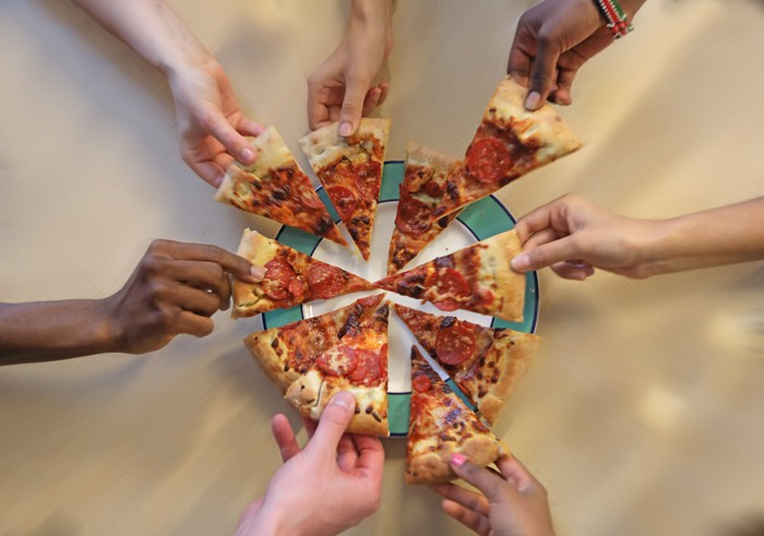 Seven hands taking slices of pizza.