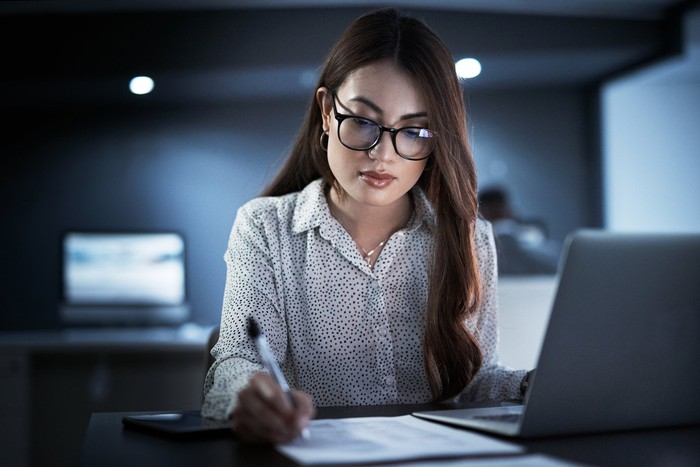 An accountant sitting in an office in front of a computer and writing on a document.