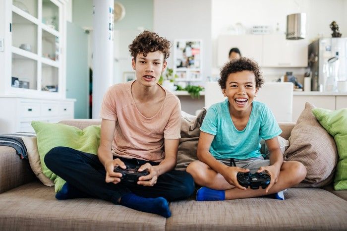 Two boys sitting on a couch and playing video games.