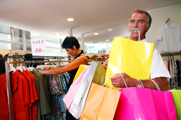 A couple shopping, with a man carry an overwhelming number of bags.