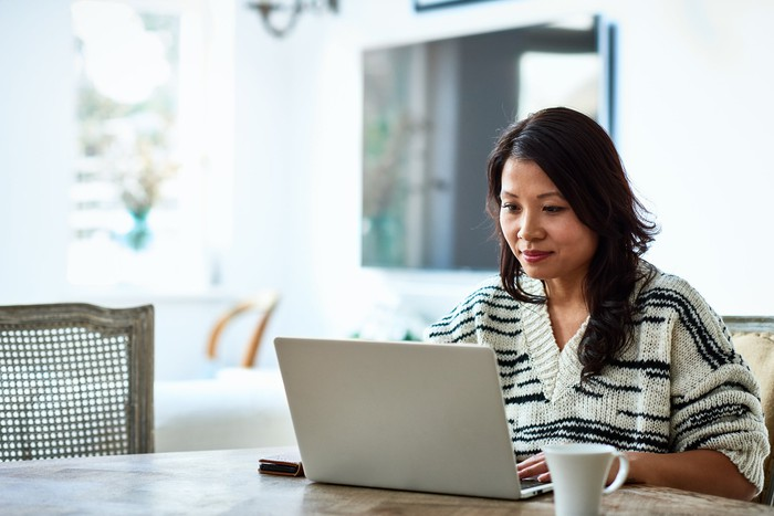 Mature person sitting at a table with a mug in front of them uses a laptop.