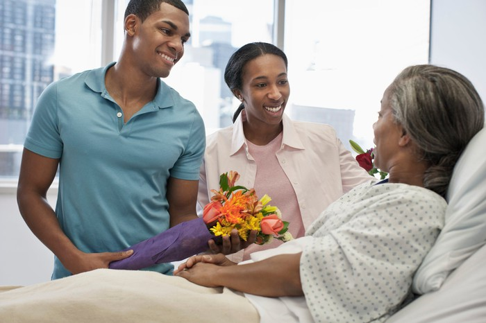 Two young adults bringing flowers to an older person lying in a hospital bed.