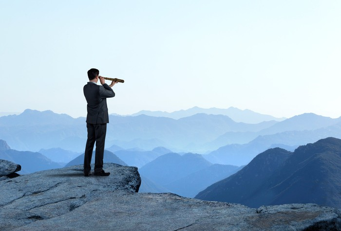 A person standing on a cliff uses a telescope to look out toward a horizon full of mountain ranges.