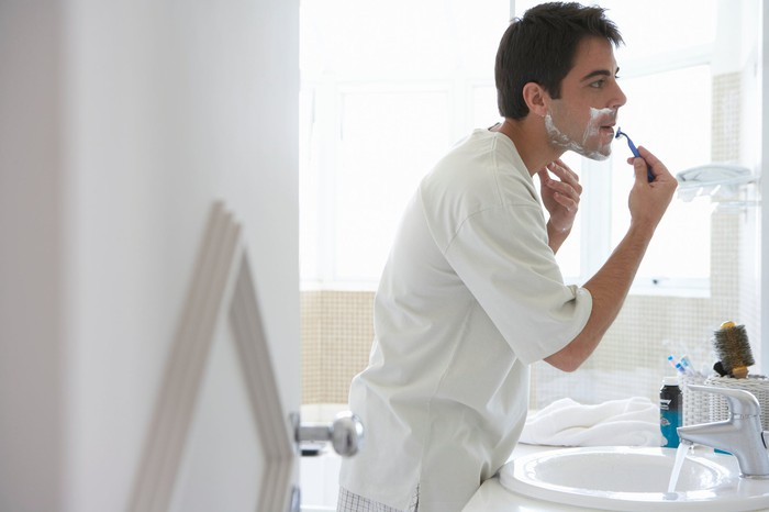 Person shaving while looking in mirror.