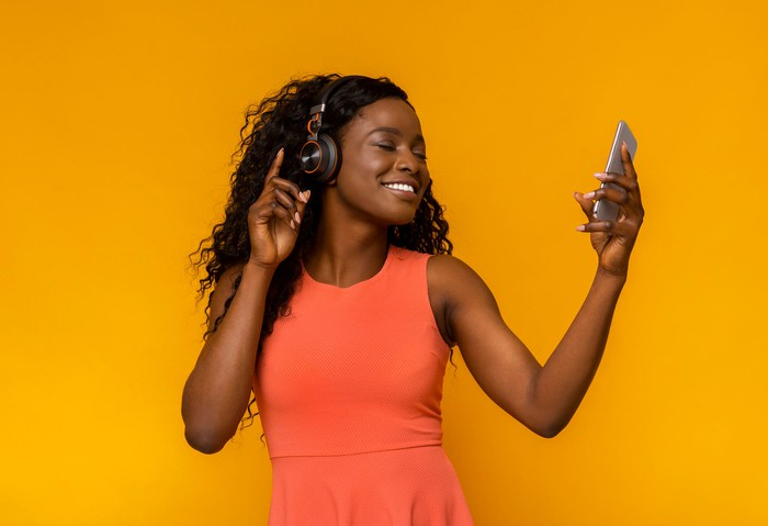 A smartphone user listens to music with headphones.