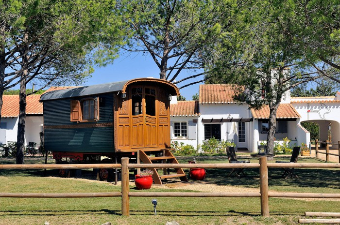 A tiny home in the shape of a wooden wagon.