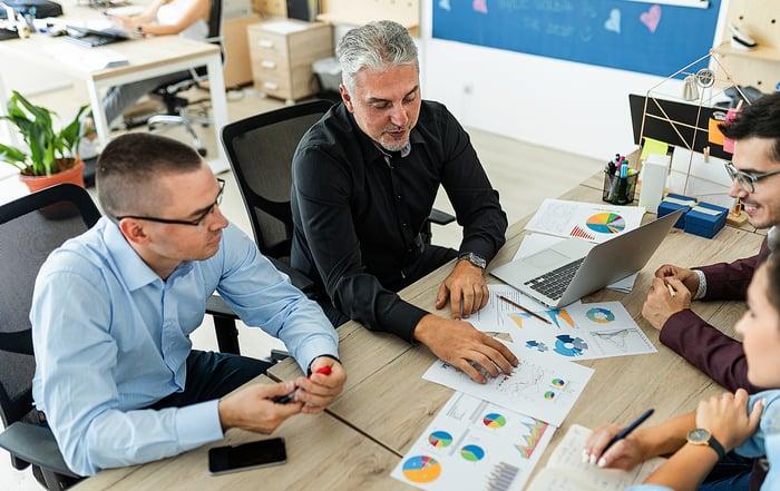 Quatre collègues sont assis autour d'une table et examinent plusieurs impressions de données de vente.